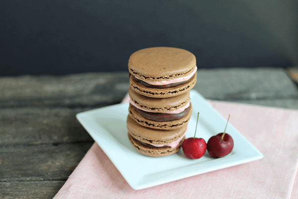 a stack of chocolate macarons filled with cherry buttercream frosting and chocolate ganache