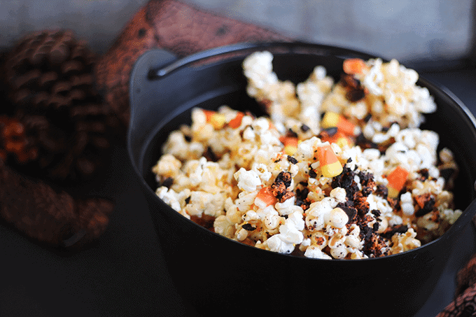 Halloween Candy Popcorn - Sweet and sticky popcorn filled with cookie crumbs and candy corn. The perfect snack to munch on while you're watching some spooky Halloween flicks!