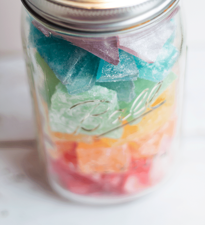 overhead image of a mason jar filled with various colors of homemade rock candy