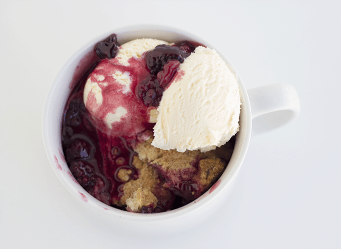 Blackberry Cobbler in a mug topped with a scoop of vanilla ice cream