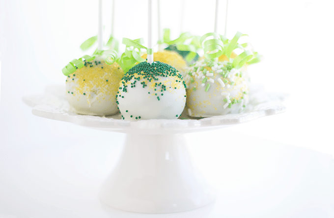 chocolate mint cake pops decorated for St. Patrick's Day, sitting on a white cake pedestal