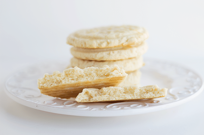 Glazed Lemon Cookies stacked on a plate. One cookie is broken in half so you can see the inside