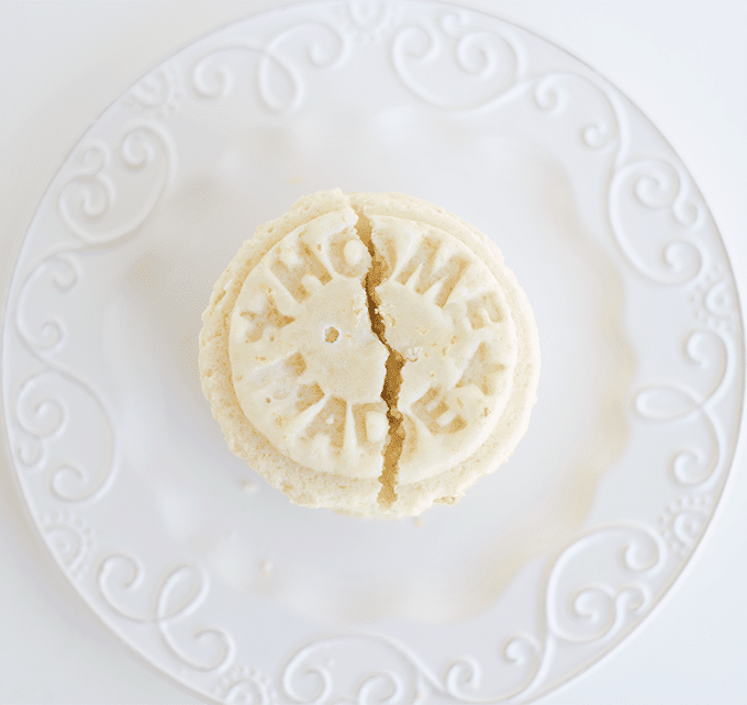 homemade lemon cookies on a plate, with one cookie broken in half