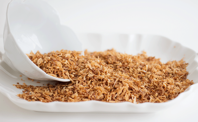 scooping homemade toasted coconut from a white tray
