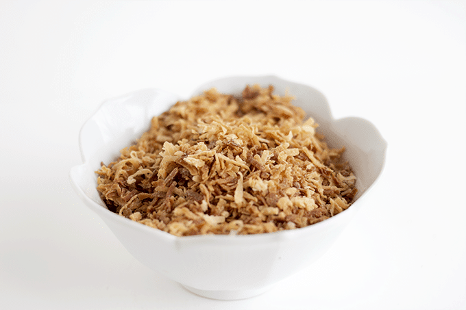 a white bowl filled with toasted coconut