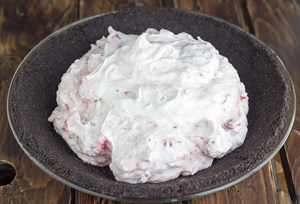 Raspberry Cream Pie filling being added to a chocolate cookie pie crust