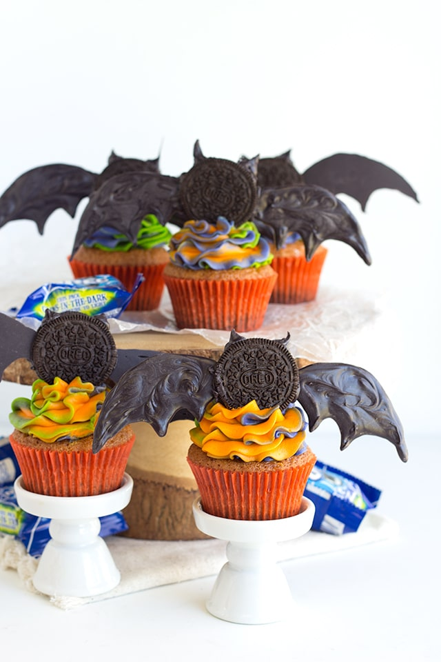 Oreo Crusted Orange Fanta Cupcakes - Adorable bat topped orange flavored cupcakes with a cute swirl of Halloween colored frosting! The cupcakes are also dipped in a orange Fanta glaze and crusted with Oreos for an extra touch.
