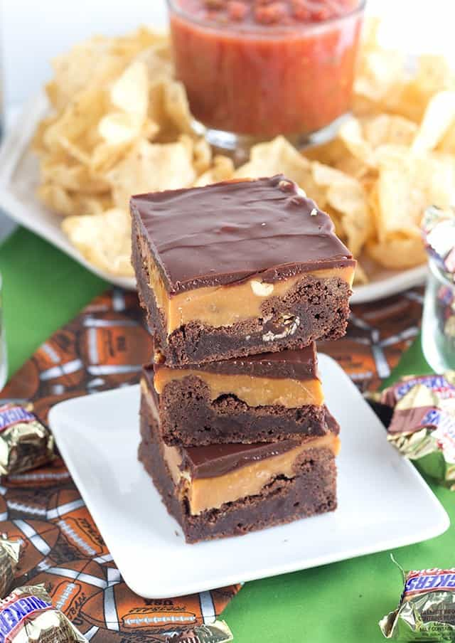 Snickers Brownies - a fudgy brownie stuffed with mini snickers and layered with caramel, peanuts and milk chocolate ganache.