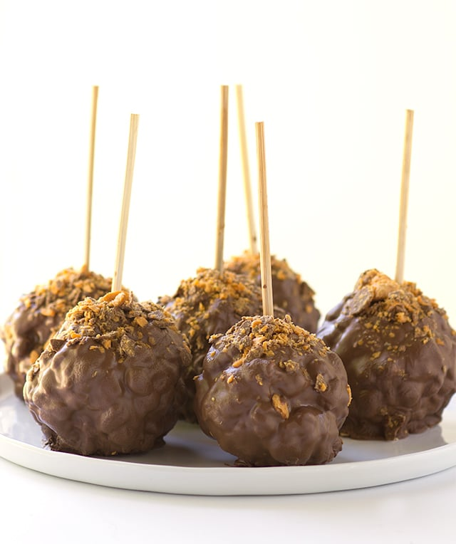 Chocolate Covered Peanut Butter Popcorn Balls - gooey peanut butter marshmallow popcorn balls coated with chocolate and sprinkled with butterfinger bits!
