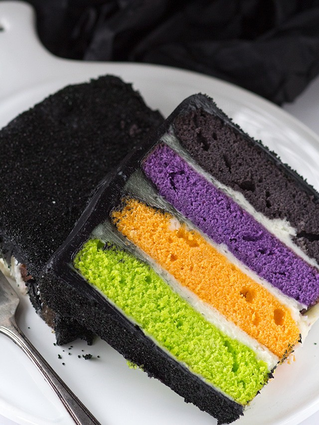 slice of Halloween layer cake showing 4 layers, each in a different color. purple, black, orange, and green