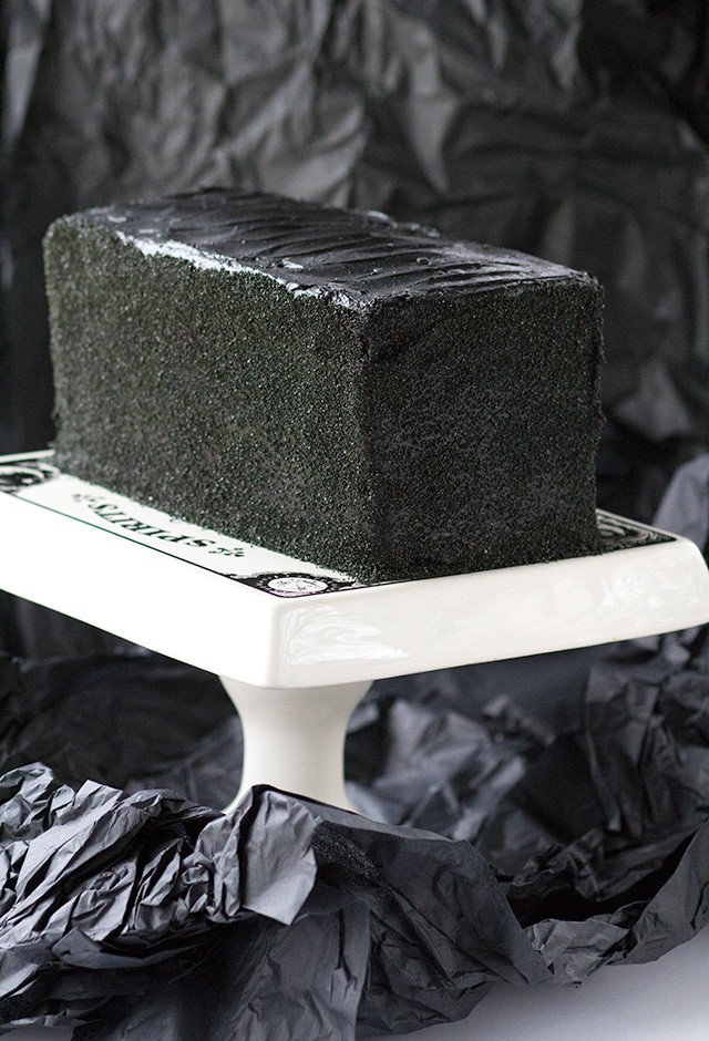 Black Halloween Cake sitting on a Halloween themed cake stand