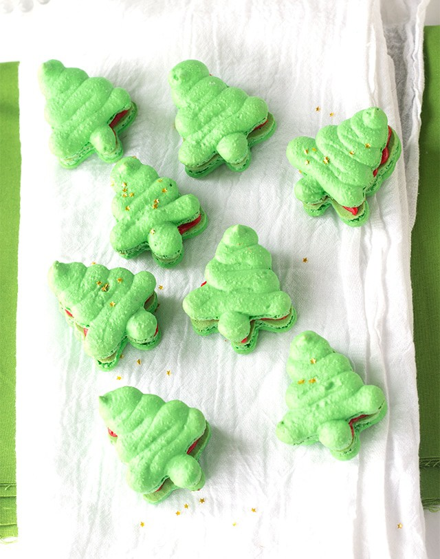 green French macarons shaped like Christmas trees filled with red frosting