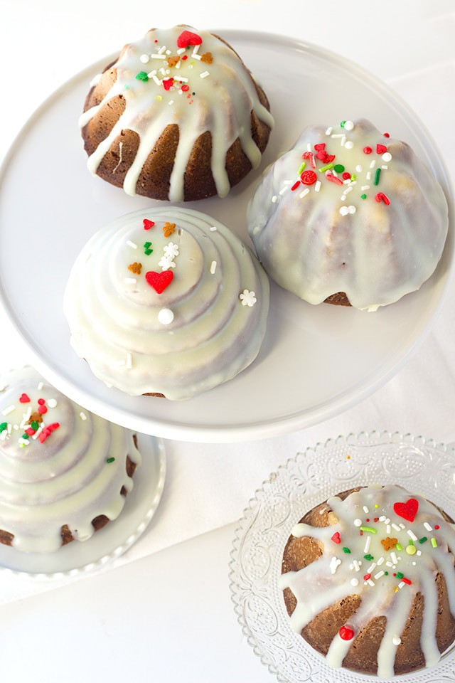 Gingerbread Bundt Cakes - the perfect little cakes for Christmas, They're full of molasses , spices, and the perfect gingerbread flavor! Top the cakelettes with a white chocolate ganache and sprinkles for the finishing touch.