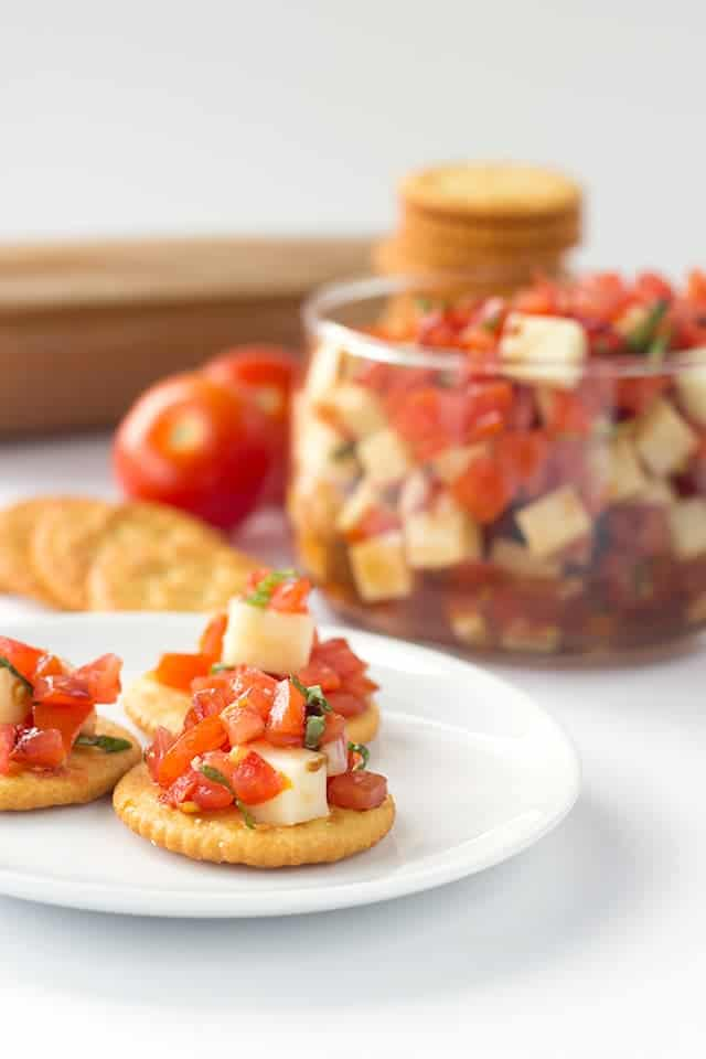 Caprese Salsa - finely diced tomatoes, shallots, basil and mozzarella tossed in a balsamic glaze and scooped up with some buttery ritz crackers!