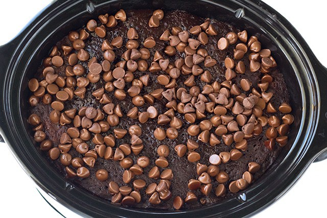 crockpot full of chocolate lava cake with chocolate chips on top
