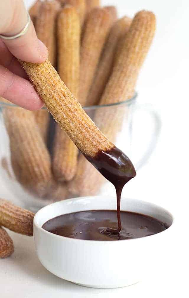 Baked Churros standing in a clear glass coffee mug. One churro being dipped into melted chocolate