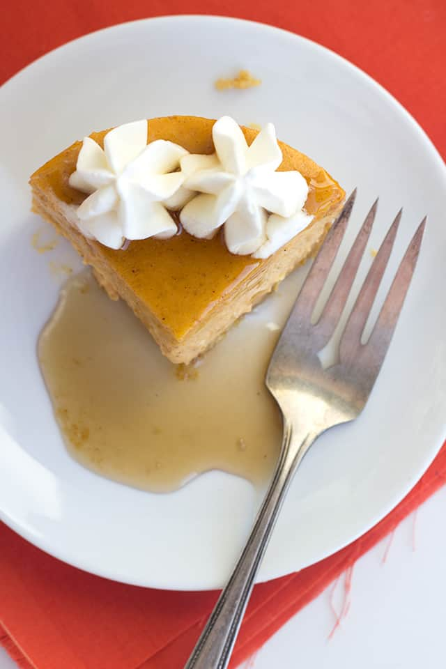 a slice of creamy maple pumpkin cheesecake on a dessert plate with a fork. The cheesecake has maple syrup and dollops of whipped cream on top