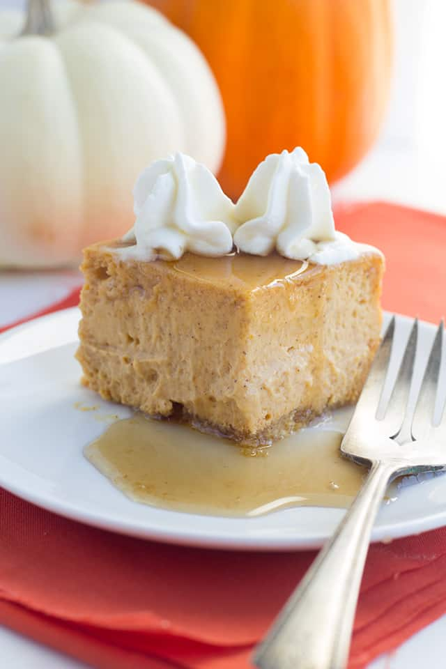 square slice of baked pumpkin cheesecake covered in maple syrup sitting on a white dessert plate with a fork